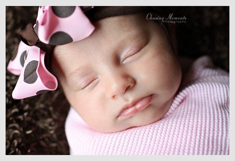 Portrait of a sleeping newborn, 1 month old baby girl, swaddled in pink blanket