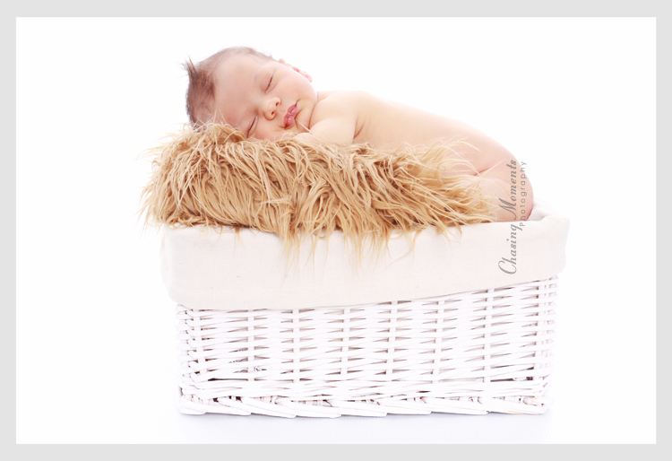 Newborn baby asleep in a basket on a white background, baby studio photography in Northern Virginia