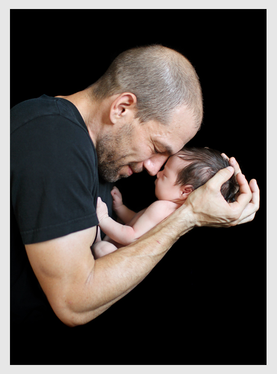 dad and newborn baby girl on black background